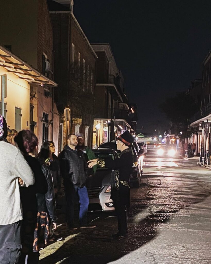 A tour guide taking NOLA visitors on a haunted walking tour of New Orleans, exploring the spooky history of the French Quarter.